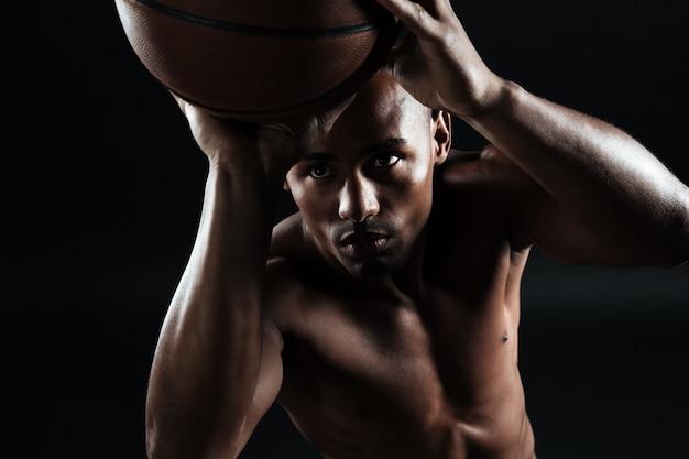 Vista del primo piano di giovane giocatore di pallacanestro afroamericano che prepara gettare palla