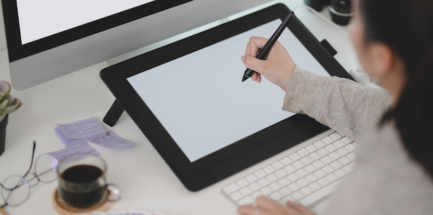 Close-up view of young female designer working on her  project while using tablet