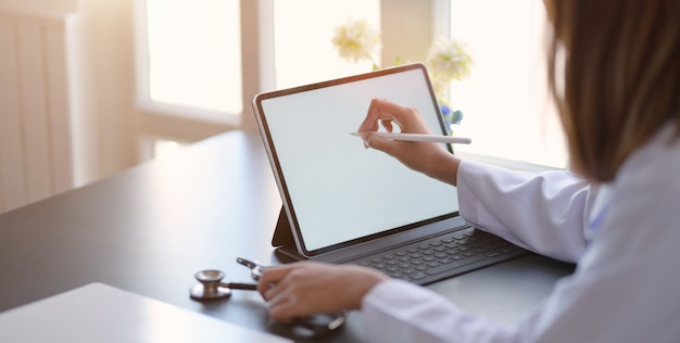 Close-up view of young female doctor writing medical charts with tablet in office room