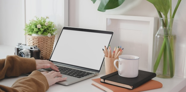 Close-up view of young female working on her project while typing on blank screen laptop