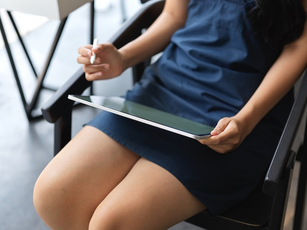 Close-up view of young female working her project with tablet while sitting in modern office room