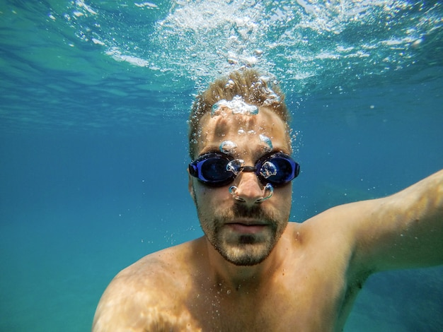 Close up view of young handsome bearded man with googles diving in the exotic turquoise sea.