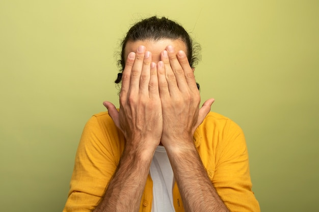 Vista ravvicinata di giovane uomo caucasico bello con gli occhiali che copre gli occhi con le mani isolate sulla parete verde oliva