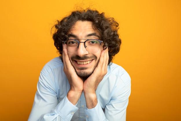 Vista ravvicinata del giovane uomo bello con gli occhiali guardando la parte anteriore isolata sulla parete arancione 88