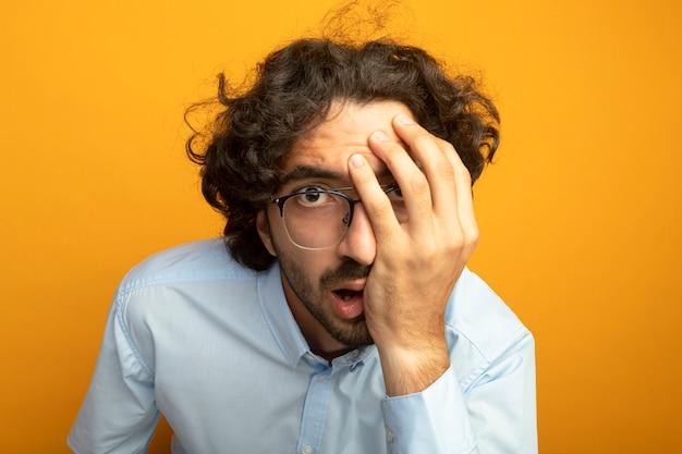 Vista ravvicinata del giovane uomo bello con gli occhiali guardando la parte anteriore isolata sulla parete arancione