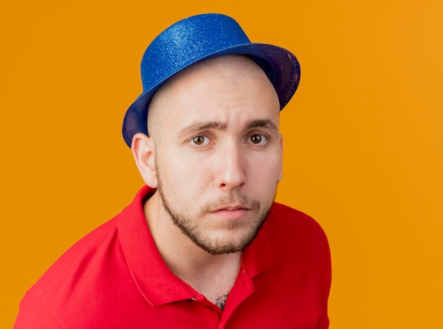 Close-up view of young handsome slavic party guy wearing party hat looking at front isolated on orange wall with copy space