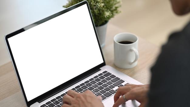 Крупным планом зрения фрилансер молодой человек работает на портативном компьютере, сидя на диване.