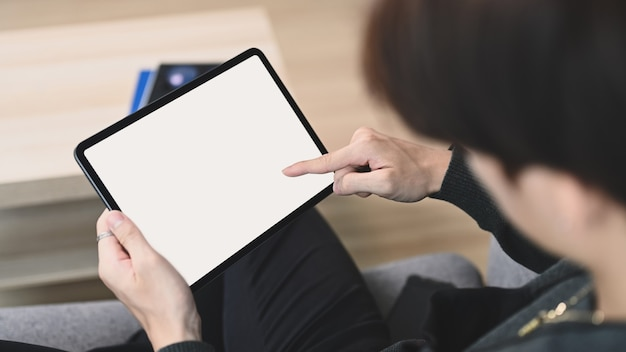 Close up view of young man holding horizontal digital tablet with blank screen while sitting on couch.