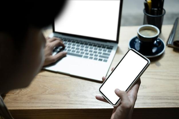 携帯電話を持ってラップトップコンピューターで作業している若い男をクローズアップします。