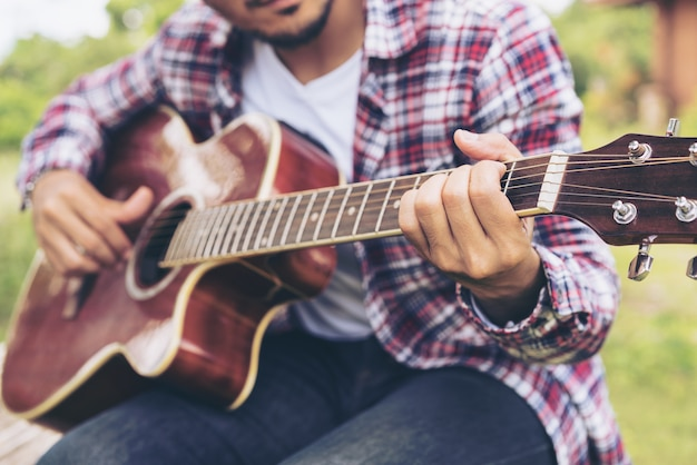 Close up view of young man playing guitar.