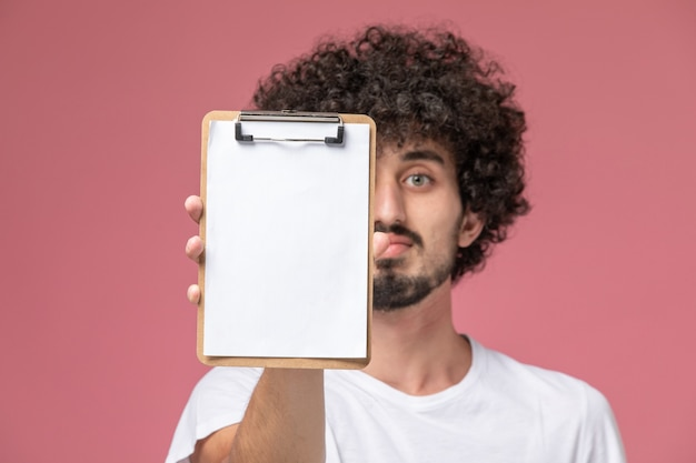 Крупным планом зрения молодой человек показывает свой офисный блокнот на камеру