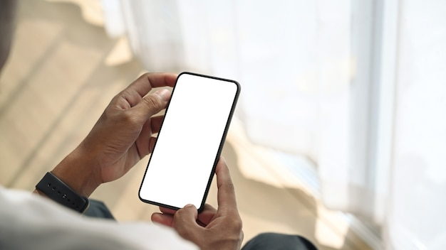 Close up view of young man sitting near window and holding mock up smart phone with white screen