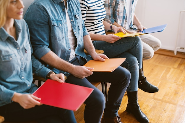 Close up view of young people sitting in chairs with folders before the job interview in the waiting room.