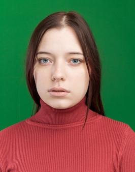 Vista ravvicinata di una giovane donna graziosa che guarda la parte anteriore isolata sul muro verde