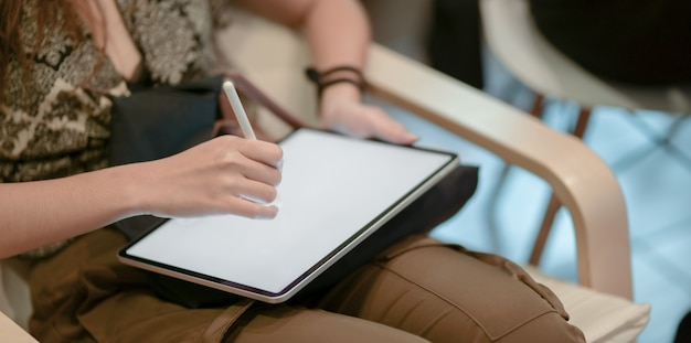 Close-up view of young professional designer working on her project while drawing on tablet
