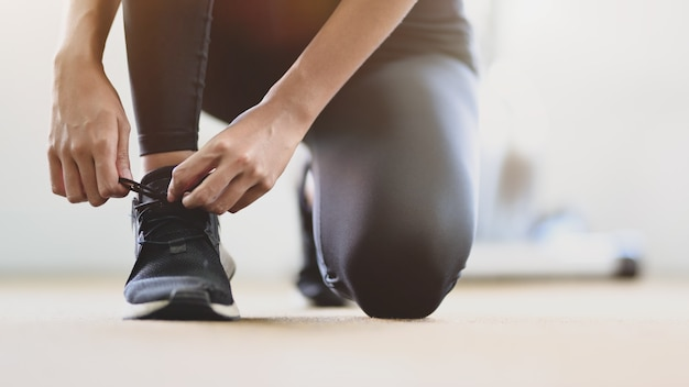 Close-up view of young slim fitness girl doing shoelaces in the sport gym