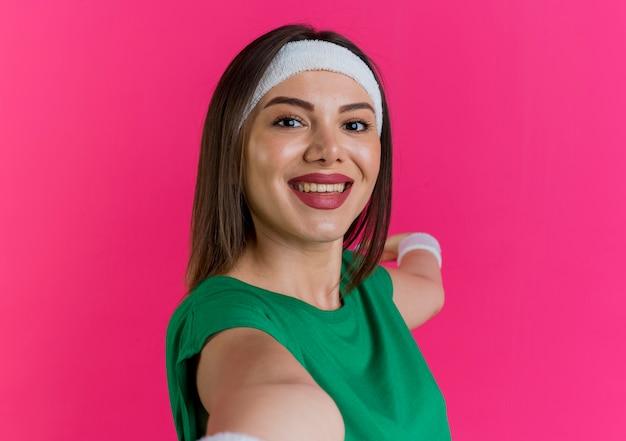 Vista ravvicinata della giovane donna sportiva che indossa la fascia e braccialetti alla ricerca e allungando le mani