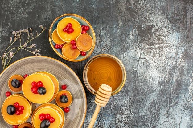Vista ravvicinata di gustose frittelle su un piatto piccolo e grande con miele