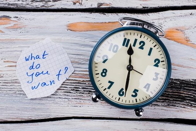 白い木の上のビンテージ目覚まし時計を閉じます。コンセプトは何が欲しいですか。