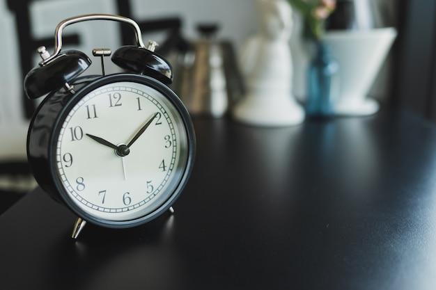 Close up vintage black alarm clock placed on a black wooden table, blurred background