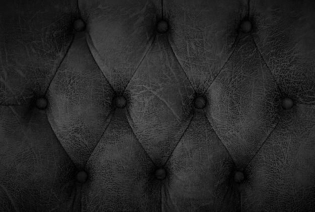 ソファの質感の背景のヴィンテージ黒革を閉じます。