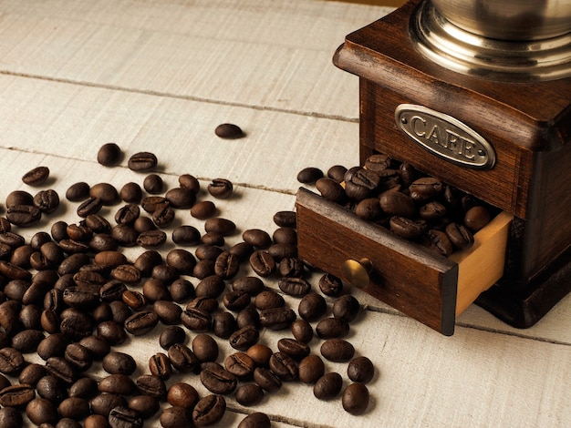 暗いと明るい木製の背景にコーヒーの穀物とクローズアップビンテージコーヒーグラインダーミル。