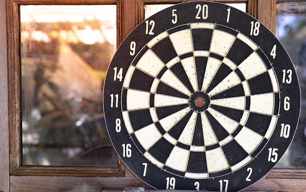Close up vintage dart board against wooden window