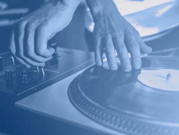 パーティーでビニールレコードの音楽を演奏するdjのヴィンテージルック、2020年のトレンドの色、クラシックなブルーのトーンをクローズアップ