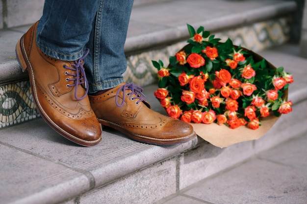 Close-up of vintage shoes with purple laces and a bouquet of roses