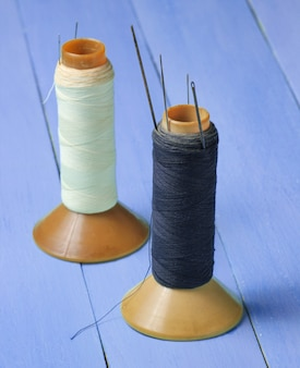 Close up on vintage thread reels with needles