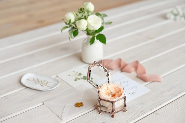 グリーティングカードと花瓶と木製のテーブルの結婚指輪のクローズアップのビンテージのウェディングジュエリーボックス。