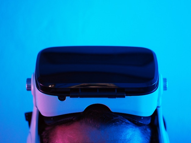 Крупный план. шлем виртуальной реальности на голове. неоновый свет вокруг.
