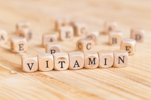 Close up vitamin word made from wooden letters on the table