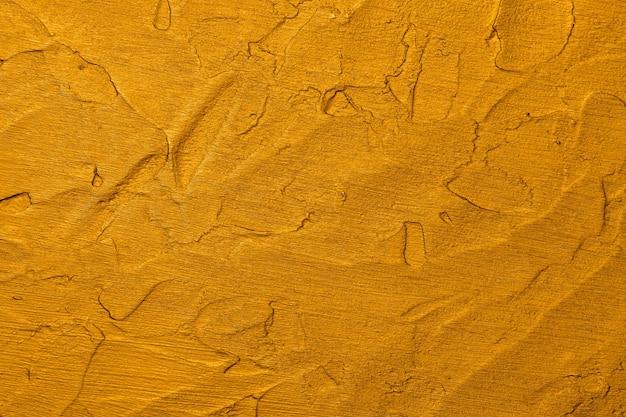 석고와 페인트의 브러쉬 스트로크와 고르지 않은 그런지 표면의 생생한 황금 노란색 추상적 인 배경 질감을 닫습니다