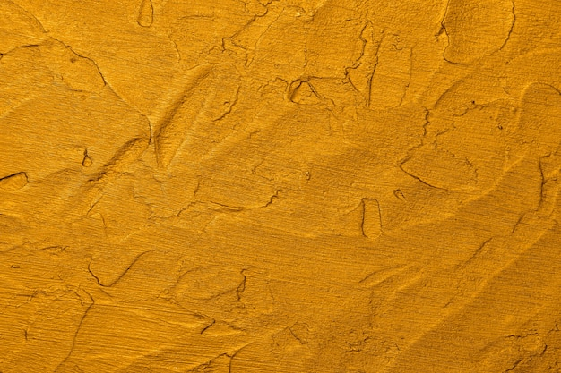 Close up vivid golden yellow abstract background texture of uneven grunge surface with brushstrokes of plaster and paint