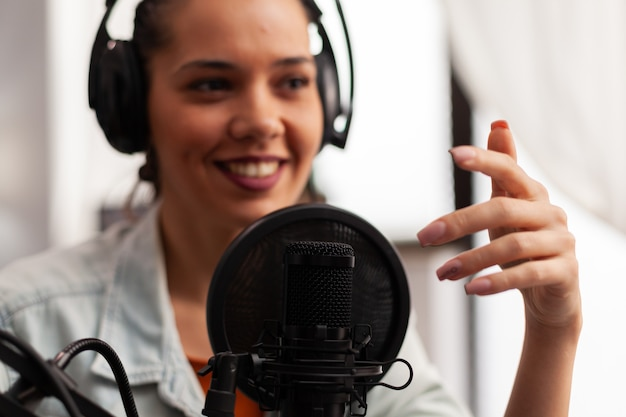 Close up of vlogger speaking at podcast microphone gesturing during life video vlog. social media content creator recording fashion video for online channel sharing advices for followers community