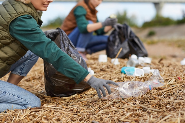 Close-up of volunteers cleaning the ground near the river in the nature