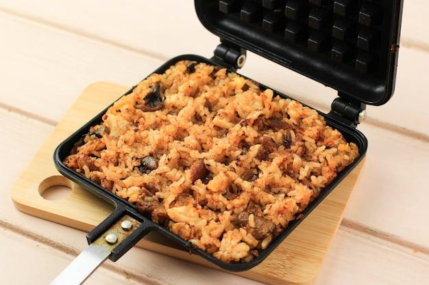 Close up waffle kimchi fried rice (kimchi bokkeumbap) или nasi goreng waffle, модный вирусный рис, прессованный с помощью вафельницы, популярный в южной корее