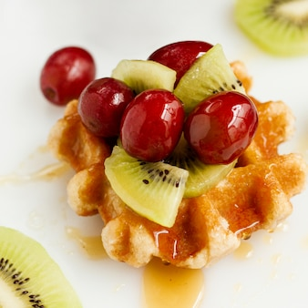 Close up waffle with honey and mix of fruits