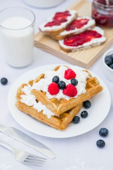 Close-up of waffle with strawberries and milk on table