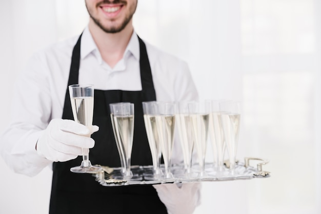 Close-up waiter holding champagne glasses