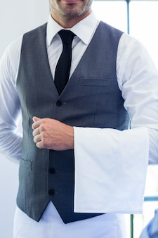 Close-up of waiter standing with napkin