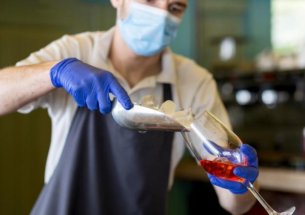 Cameriere del primo piano con i guanti che preparano la bevanda