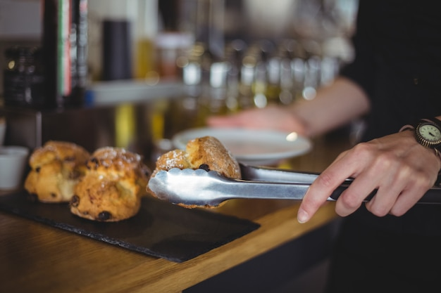 Close-up of waitress serving muffin in a plate at counter
