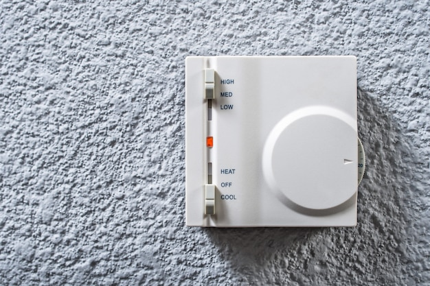 Close-up wall-mounted control panel for air conditioning in a room