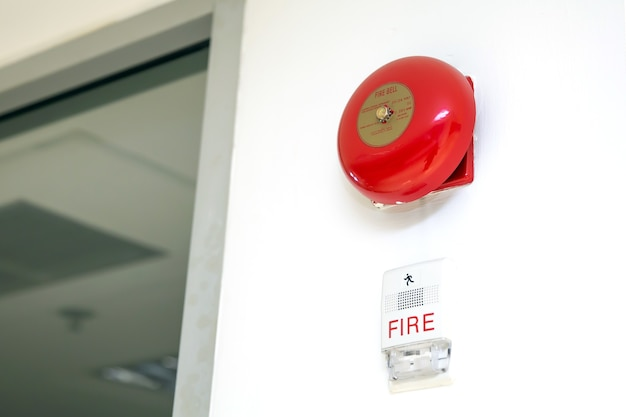 Close-up wall mounted red fire bell and flashing warning light in the building concepts of fire alarm prevention and safety system