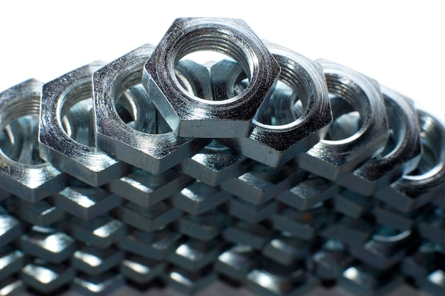 Close-up wall of numerous chrome metal nuts in the form of honeycombs next to each other