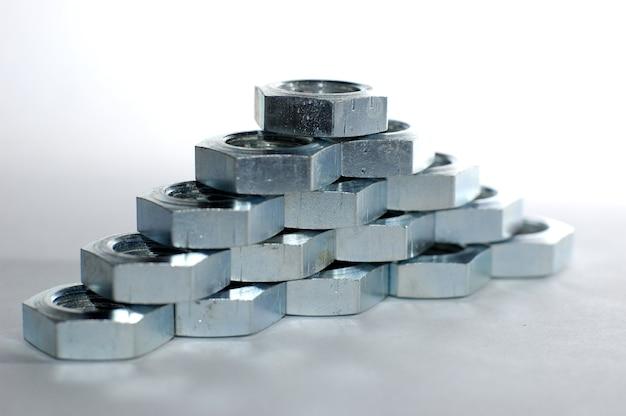 隣接するハニカムの形をした多数のクロム金属ナットのクローズアップ壁。