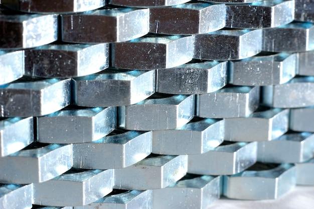 서로 옆에 벌집 형태의 수많은 크롬 금속 너트의 근접 벽.