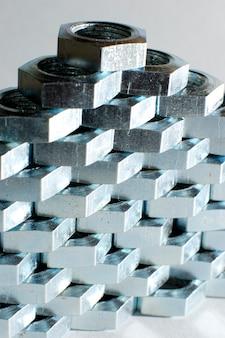 서로 옆에 벌집 형태의 수많은 크롬 금속 너트의 근접 벽